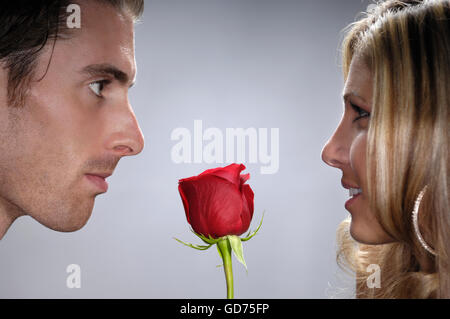Young man with a red rose facing a young woman - Stock Photo