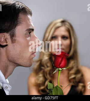 Young man with a red rose standing in front of a woman - Stock Photo