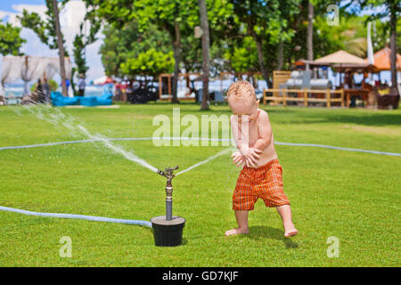 Happy baby boy playing with sprinkler spray and splashing with fun under water drops on beach club green grass lawn. - Stock Photo