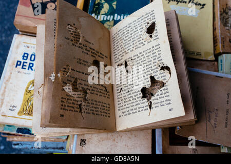 A book at the flea market eaten by bookworms in Vietnam - Stock Photo