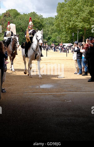 Soldiers of The Blues and Royals entering the stabling at Horse Guards Parade - Stock Photo