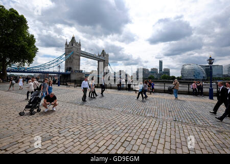Tourists on Victoria Embankment London with Tower Bridge on the left and City Hall on the right in the background - Stock Photo