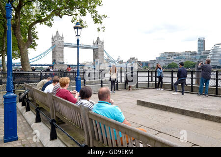 Tourists sit on benches Victoria Embankment alongside the Thames. Tower Bridge in the background and City Hall and - Stock Photo