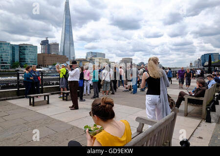 London, United Kingdom. Tourists on Victoria Embankment along the Thames river looking at Tower Bridge. The Shard - Stock Photo
