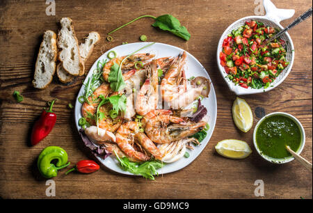 Grilled tiger prawns in white plate served with bread, green salad, lemon slices, peppers and pesto sauce on wooden - Stock Photo