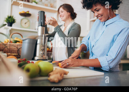 Young african woman cutting fruits at bar counter, with coworker using juicer in background. Two female working - Stock Photo