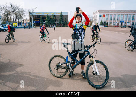 Gomel, Belarus - April 10, 2015: Young man cyclist taking photo on smartphone at opening of the cycling season in - Stock Photo