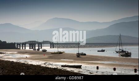 UK, Wales, Gwynedd, Barmouth, boats moored on Mawddach Estuary near Railway Viaduct at low tide - Stock Photo