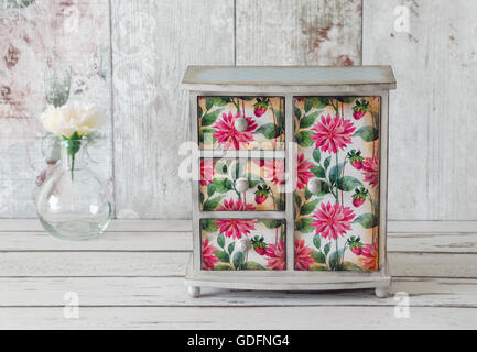 Handmade mini wardrobe decoupaged in a floral pattern on a shabby chic background - Stock Photo