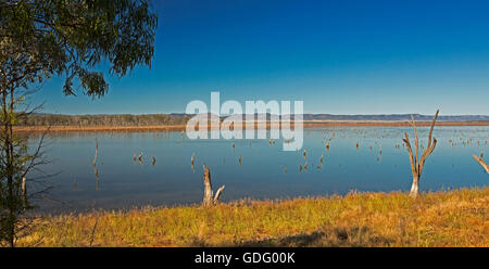 Panoramic view of vast blue waters of Lake Nuga Nuga with rugged Carnarvon ranges on horizon under blue sky in outback - Stock Photo
