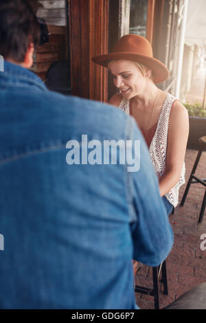 Young caucasian woman wearing hat sitting at a coffee shop with her male friend. Young friends sitting at a cafe - Stock Photo