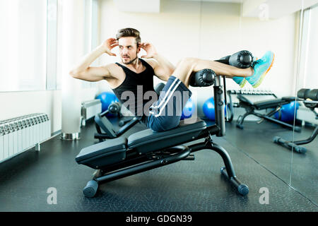 Young man doing exercises for abdominal muscles at the gym - Stock Photo