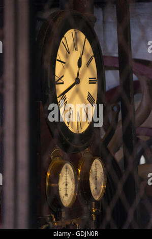 Old factory time clock with pressure gauge - Stock Photo