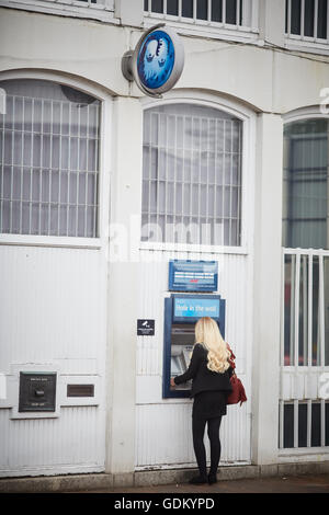 Wilmslow Barclays bank cash machine atm  Young lady girl woman she using cash machine in street town centre single - Stock Photo