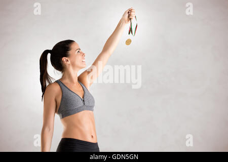 Fit woman holding a medal on a gray background - Stock Photo