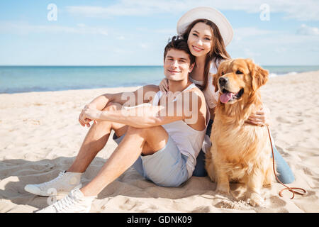 Young beautiful couple in love playing with their dog on the beach - Stock Photo