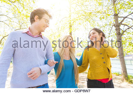 Friends walking on street, linking arms face to face smiling - Stock Photo