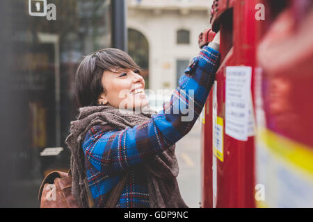 Young woman posting letter - Stock Photo