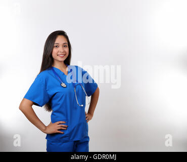 A young hispanic nurse in blue scrubs. - Stock Photo