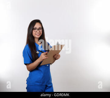 A young hispanic nurse in blue scrubs wearing glasses. - Stock Photo