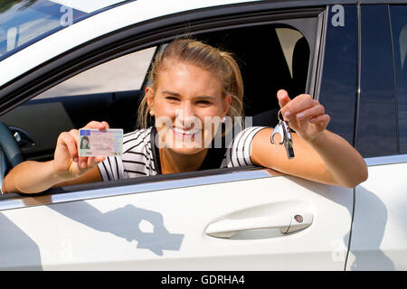 Young woman in a car with driver license and car key in the hand - Stock Photo