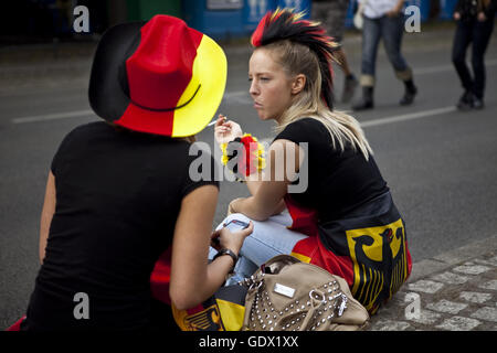 Two women sit on the German Fan Mile (Fanmeile) at the World Cup in Berlin, German, 2010 - Stock Photo