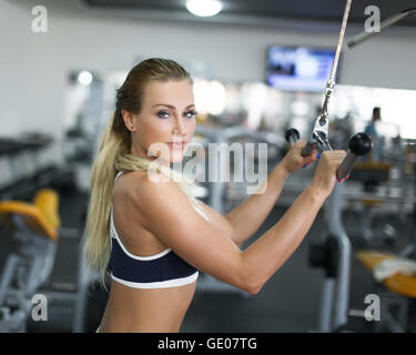Woman doing exercise on triceps machine in gym - Stock Photo