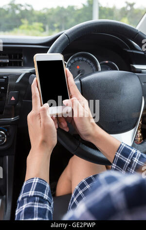 Young female driver using touch screen smartphone in a car. - Stock Photo