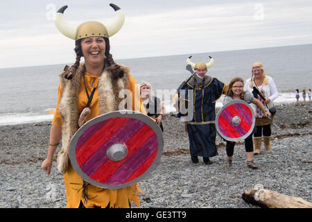Aberystwyth Wales UK, Saturday 23 July 2016  A group of people in Viking  fancy dress costumes running up the beach - Stock Photo