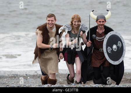 Aberystwyth Wales UK, Saturday 23 July 2016  Three People in Viking fancy dress costumes running up the beach taking - Stock Photo