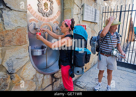 Pilgrims filling a glass of wine in Winery Irache. fountain that offers water and wine to the pilgrim. Irache. Navarra.Spain. - Stock Photo