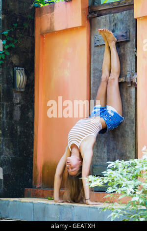 Young woman doing yoga, handstand on door - Stock Photo