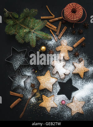 Cooked Christmas holiday traditional gingerbread cookies with sugar powder, anise and cinnamon sticks on black background - Stock Photo