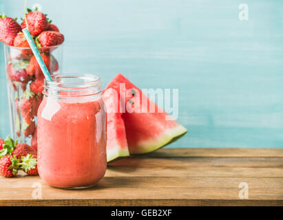 Freshly blended red fruit smoothie in glass jar with straw - Stock Photo
