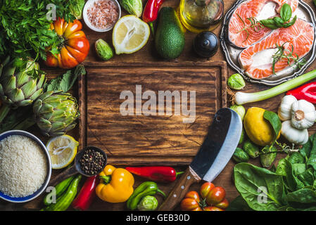 Raw uncooked salmon fish with vegetables, rice, herbs, spices and wine on chopping board over rustic wooden background - Stock Photo
