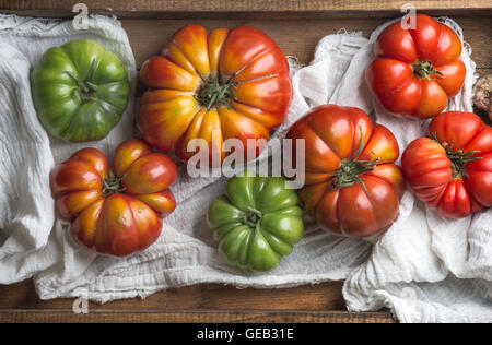 Colorful Heirloom tomatoes in rustic wooden tray - Stock Photo