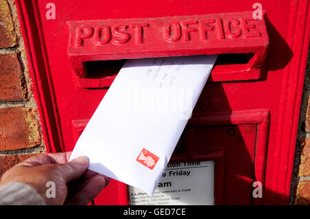 Posting letter in Royal Mail wall pillar box, Stanwell Moor, Surrey, England, United Kingdom - Stock Photo