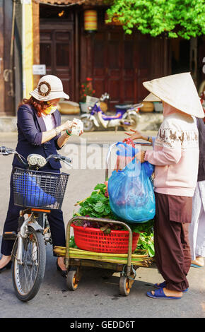 Hoi An, Vietnam - February 17, 2016: Asian buyer and trader in a traditional vietnamese hat selling fresh green - Stock Photo