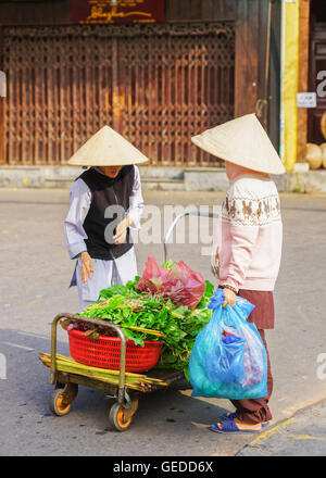 Hoi An, Vietnam - February 17, 2016: Asian buyer and trader in a traditional vietnamese hat selling fresh spinach - Stock Photo