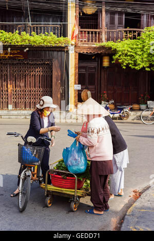 Hoi An, Vietnam - February 17, 2016: Asian buyer and trader in a traditional vietnamese hat selling green spinach - Stock Photo