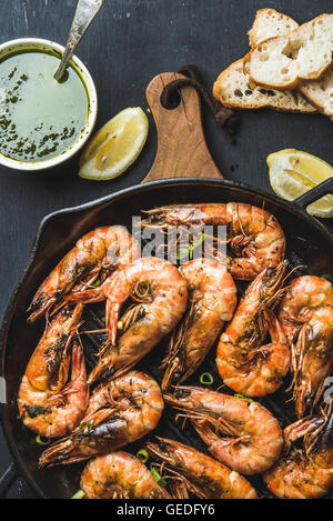 Roasted tiger prawns in iron pan on wooden board with fresh leek, lemon slices, bread and pesto sauce over black - Stock Photo