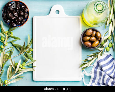 Two bowls with pickled green and black olives, olive tree sprigs, oil in glass bottle, white ceramic board in center - Stock Photo
