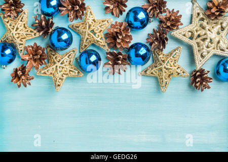 Christmas or new year decoration background: pine cones, blue glass balls, golden stars on painted backdrop, copy - Stock Photo