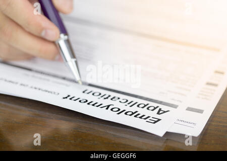 Businessman fill in Employment Application form with pen. job vacancy concept or business employment concept. - Stock Photo