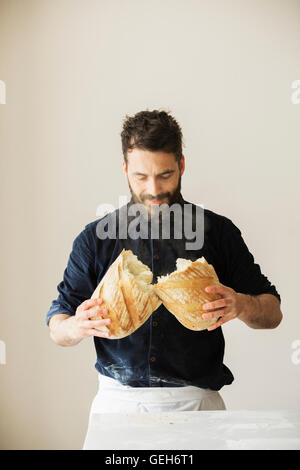 Baker holding two freshly baked loaves of bread. - Stock Photo