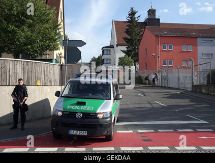 Zirndorf, Germany. 27th July, 2016. A policeman standing next to a police car near the preliminary reception centre - Stock Photo