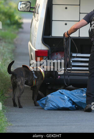 Zirndorf, Germany. 27th July, 2016. A sleuth dog and a police official examine a burned out suitcase in a blue plastic - Stock Photo