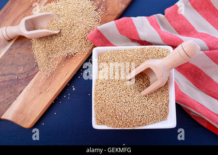 White grain quinoa with wooden scoops and chopping board on dark blue wood background. - Stock Photo