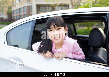 Cute little Chinese girl leaning out of car window - Stock Photo