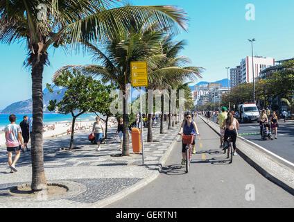 Active residents and tourists stroll along near Posto 9 on Ipanema beach, - Stock Photo